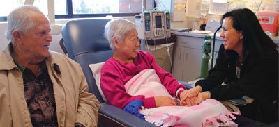 Oncology Certified Nurse Caroline Bailey, right,comforts cancer patient Nobue Chowanec and her husband Emile.